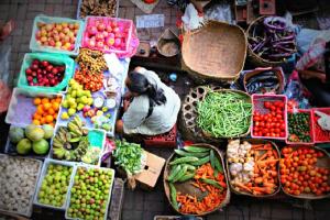 Dans le marché d'Ubud à Bali, vue du haut, une femme est au mileu de fruits et légumes. Un mélange incroyables de couleurs.